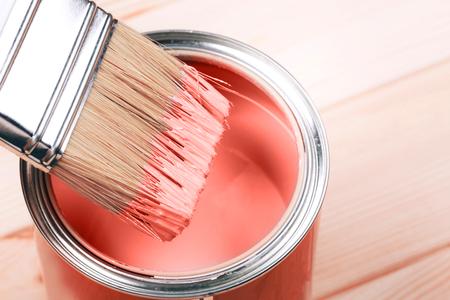 Pincel con pintura Living Coral sobre fondo de madera. Color del año 2019. Concepto de tendencia principal. Foto de archivo