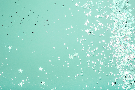 Silver and pink star glitter on teal pastel background. Festive concept. Place for design. 免版税图像