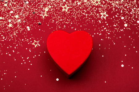 Heart shaped box with golden glitter and star confetti on red festive background. Valentines holiday concept. Top view.