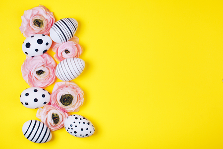 Creative graphic hand-painted eggs and ranunculus flowers on bright yellow background. Easter concept.