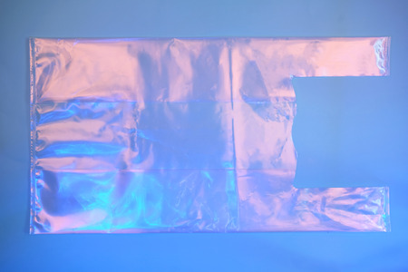 Plastic bag on trendy blue neon background as symbol of environmental problem. Ecology concept.