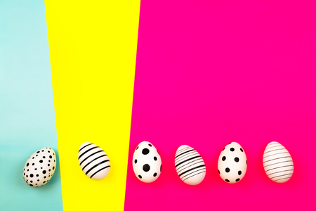 Different graphic hand drawn eggs on bright background in trendy colors. Easter concept. Place for text.