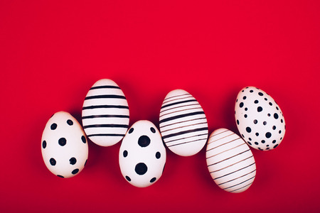 Different graphic hand-painted eggs on bright red background. Easter concept. Flat lay style.