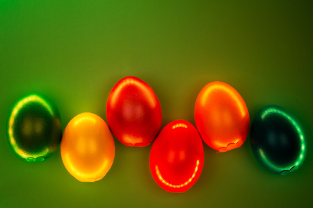 Creative photo of colorful eggs in neon lights on green background. Easter concept. Flat lay style.