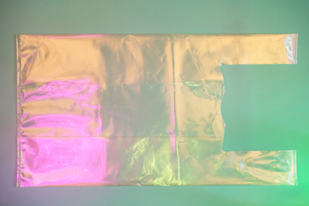 Plastic bag on trendy pink and green background as symbol of a major environmental problem. Ecology concept.