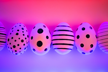 Different graphic hand-painted eggs in Proton Purple neon light. Easter concept. Top view. Imagens