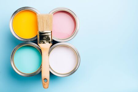 Brush with wooden handle on open cans on blue pastel background. Yellow, white, pink, turquoise colors. Renovation concept. Place for text.