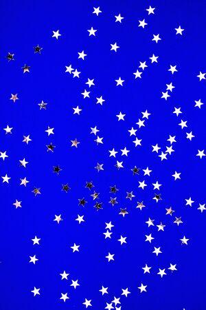 Silver stars glitter on blue background. Festive holiday pastel backdrop.