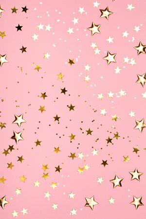 Golden stars glitter on pink background. Festive holiday pastel backdrop. Фото со стока