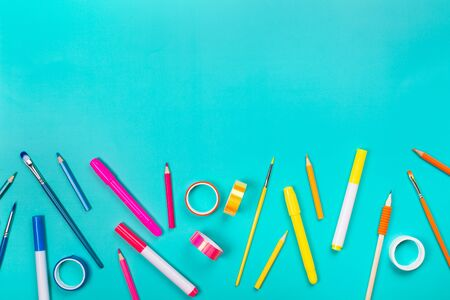 School items as a frame on blue background. Trendy colors, flat lay style. Back to school concept.