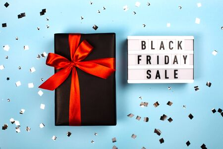 Lightboard with letters and black gift box with red ribbon. Black friday sale concept. Фото со стока