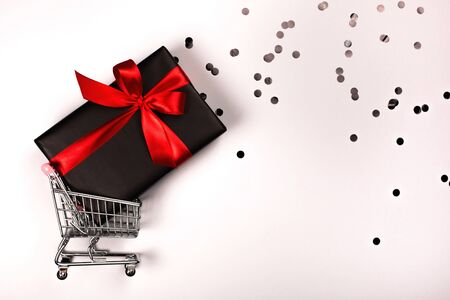 Gift box with red bow in a metal shopping basket with place for text. Фото со стока