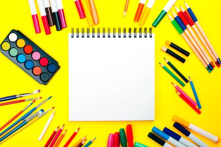 School supplies on yellow background and note book with copy space. Back to school concept. Фото со стока
