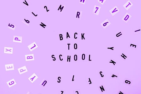 Back to school concept. Letters on purple background. Фото со стока