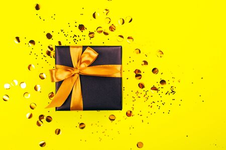 Black gift box with golden bow on yellow background with glitter. Holiday concept. Фото со стока