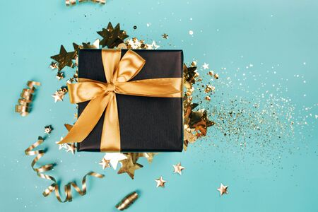 Black gift box with golden bow on turquoise background with glitter. Holiday concept.
