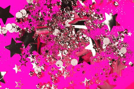 Silver sparkles on pink background. Holiday concept.