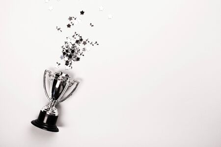 Champion cup on grey background, Flat lay style. Open composition.