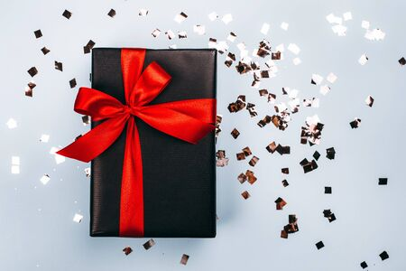 Black gift box with red ribbon on blue background. Black friday sale concept.