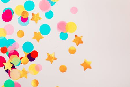Multicolor confetti on grey background. Perfect backdrop for holidays.