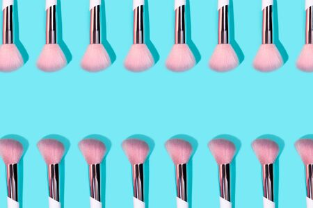 Pattern made of make up white brush on turquoise background. Minimal beauty concept.