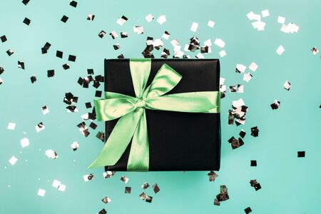 Black gift box with mint bow on turquoise background with glitter. Holiday concept.