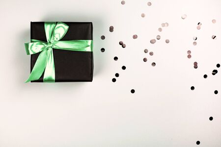 Black gift box with mint bow on white background with glitter. Holiday concept.
