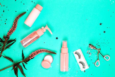 Care cosmetics on a trendy green background. Flat lay style. Фото со стока