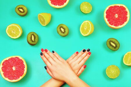 Trendy red and blue manicure on mint background with fresh fruits. Flat lay style. Banco de Imagens