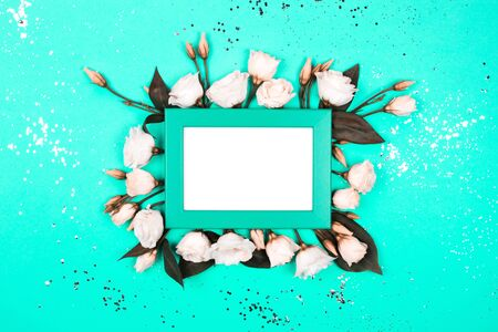 Frame with flowers and glitter in trendy colors. Flat lay style.