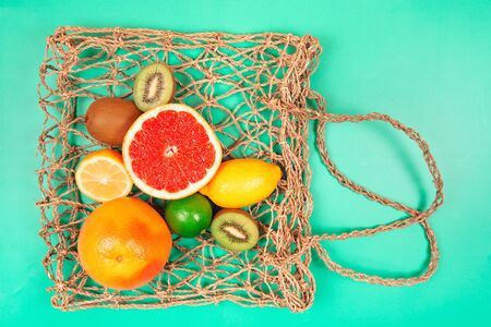 Fruits on textile bag. Trendy green background. Zero waste concept. Flat lay style.