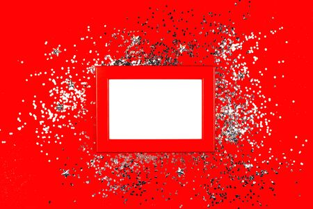 Frame on red background with silver sparkles. Flat lay style. Trendy color.