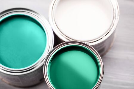 Several opened cans with green paint inside. Flat lay style