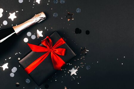 Champagne with gift box on black background. Flat lay style Фото со стока