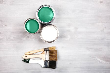 Green paint cans and colored brushes on white wooden background Фото со стока