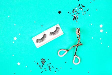 Eyelash curler and eyelashes on mint background with glitter. Flat lay style.
