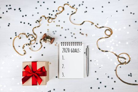 Holiday decorations and notebook with on white rustic table, flat lay style. Planning concept.