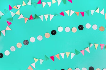 Party garlands on green pastel background. Flat lay style.