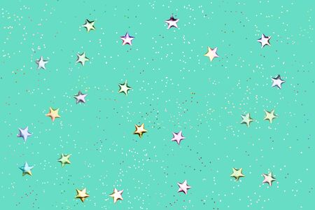 Green mint background with holographic glitter and metallic stars. Flat lay style Фото со стока