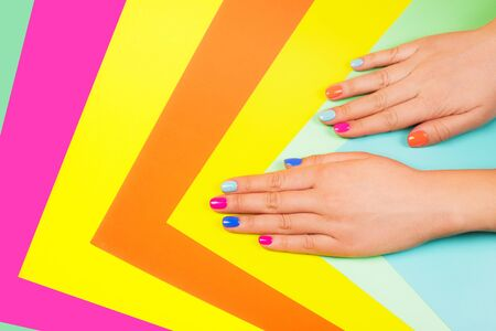 Neon manicure on multicolored bright background in trendy colors. Flat lay style. Фото со стока - 130017419
