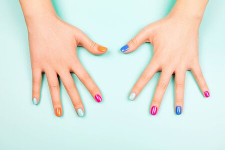 Womans hands with perfect manicure in trendy neon colors on turquoise background. Beauty concept. Фото со стока - 130017422