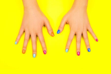 Beautiful female hands with manicure in trendy neon colors on bright yellow background. Beauty concept.