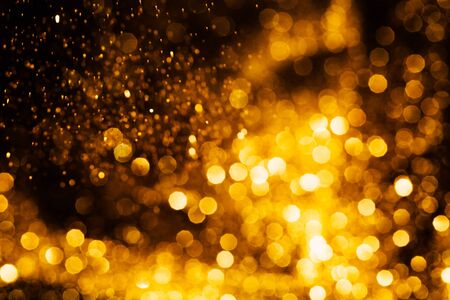 Splash of golden sparkles on black background. Фото со стока
