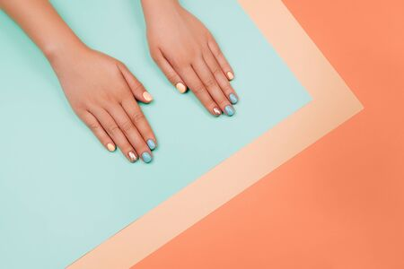 Manicure in trendy colors: coral, metallic yellow and mint on colorful background. Flat lay style.