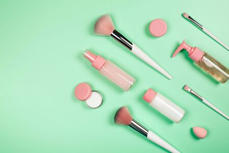 Care cosmetics in bottles on a delicate green background.