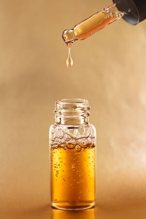 Bottle of cosmetic oil with pipette on golden background. Front view.