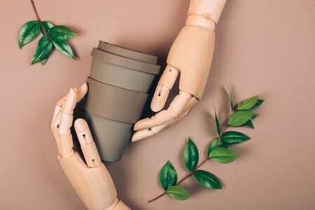 Wooden hand holding reusable cup of coffee. Concept of plastic-free and zero waste living Фото со стока - 135393453