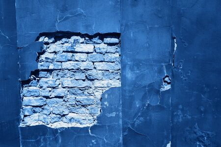Cracked and textured blue wall, plaster background. Color of the year 2020 concept.