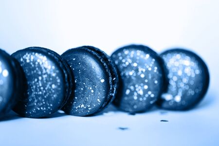 Dark blue macarons in a row with space pattern on white background.