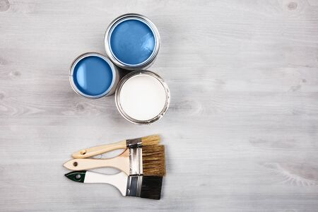 House renovation, paint cans and colored brushes on white wooden background. Blue color of paint.